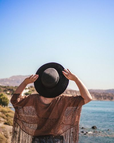 Rear View Of Woman Wearing Hat While Standing Against Clear Sky