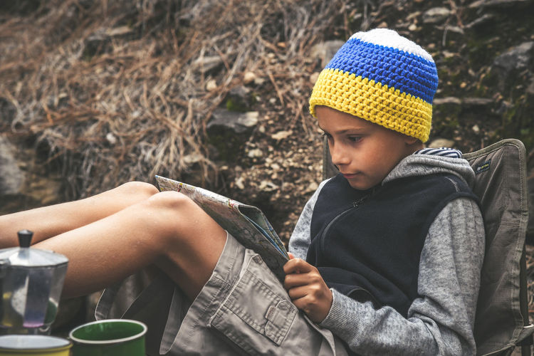 Little boy with headphone with the flag of the Canary Islands sitting with raised legs resting looking on the map of the trails in the forest. young explorer looking for adventure One Person Leisure Activity Real People Lifestyles Casual Clothing Clothing Sitting Nature Holding Looking Knit Hat Focus On Foreground Men Day Hat Front View Childhood Child Outdoors Adolescence  Innocence Warm Clothing Pre-adolescent Child