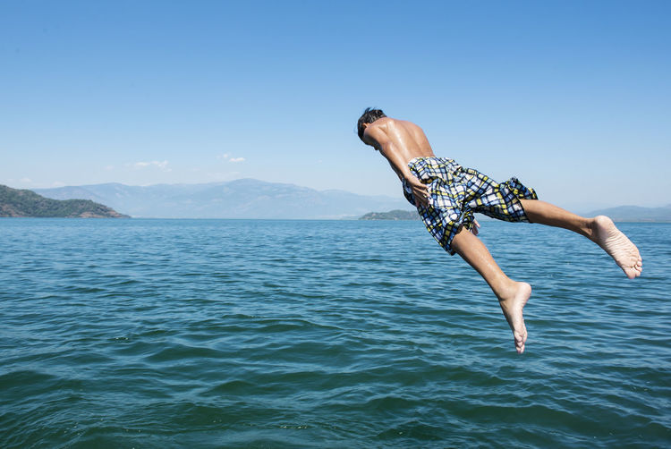 Shirtless young man jumping in sea against blue sky