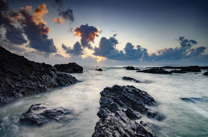 beautiful sunrise on the beach.soft wave hitting the rock.cloudy sky and sunlight background Beach Beauty In Nature Cloud - Sky Day Idyllic Landscape Nature No People Outdoors Rock - Object Rock Formation Scenics Sea Sky Sunrise Sunset Vacations Water Wave