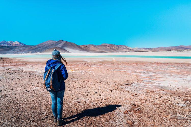 Rear view of man standing on desert against blue sky