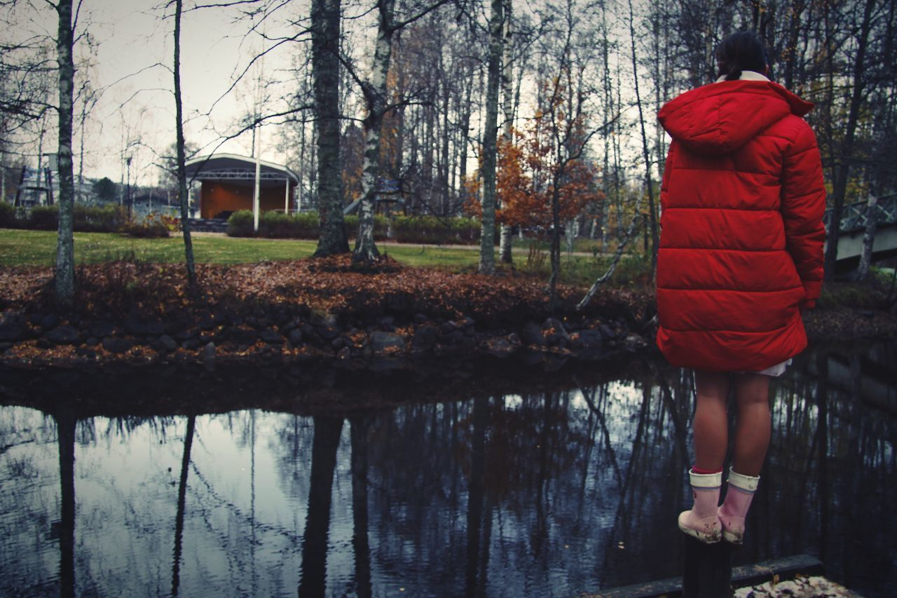 water, rear view, tree, real people, nature, one person, plant, lifestyles, clothing, day, lake, women, red, full length, reflection, leisure activity, standing, adult, outdoors, warm clothing, hood - clothing