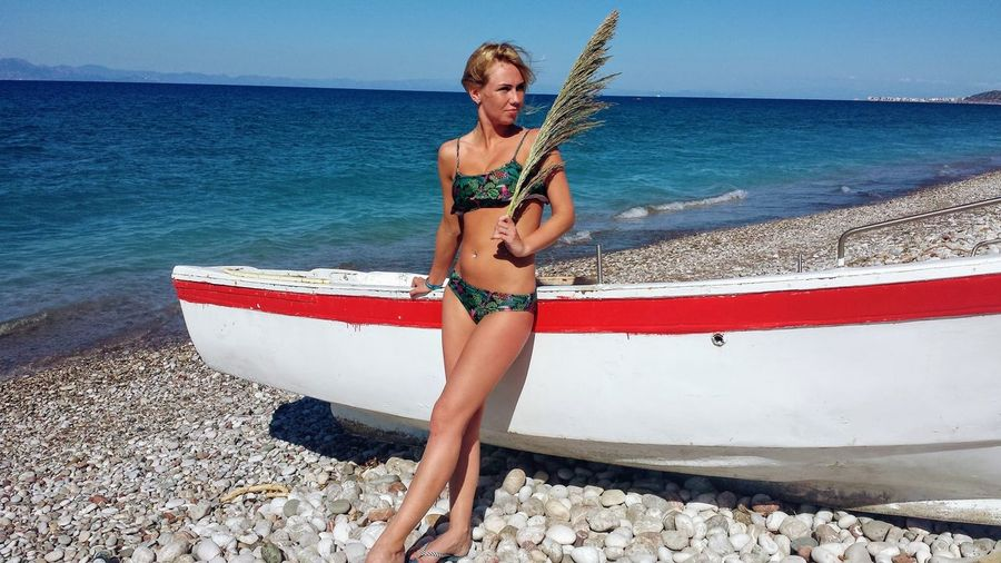 Woman wearing bikini holding grass while leaning on moored boat at beach