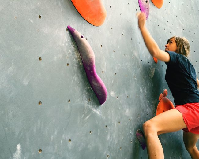 Low angle view of mid adult woman climbing wall