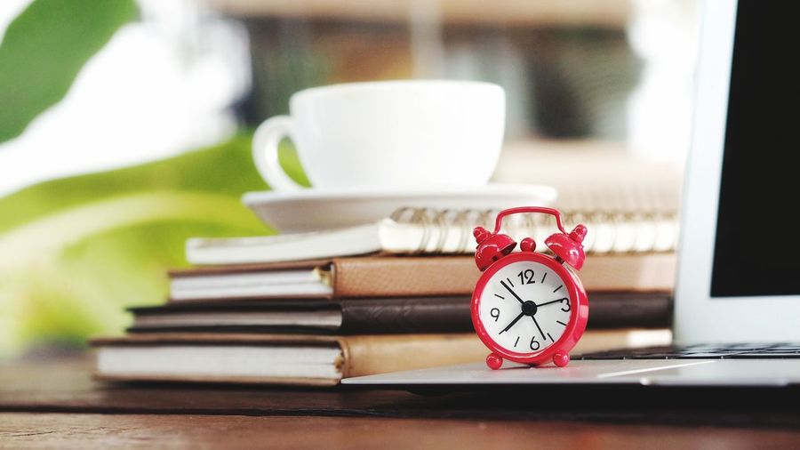 Close-up of alarm clock on laptop by stacked diaries