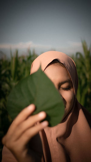 Close-up of woman holding leaf at farm