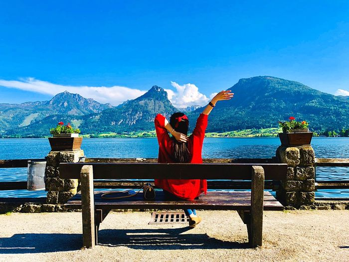 Rear view of woman sitting on bench by river against mountains