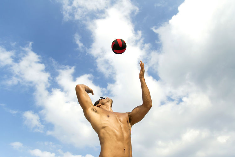 Low angle view of fit shirtless young man playing with ball against sky