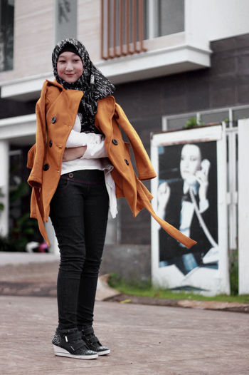 Portrait Of Woman Wearing Hijab While Standing Against Building
