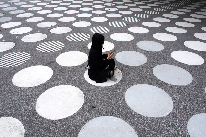 High angle view of woman sitting on tiled floor