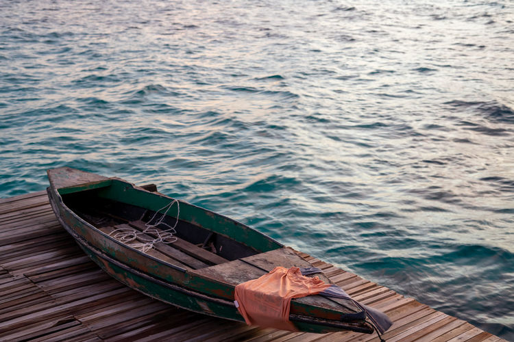 Old wooden boat sitting on the pier overlooking the beautiful semporna turquoise sea.