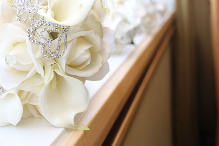 Close-up of diamond jewelry on white wedding bouquet