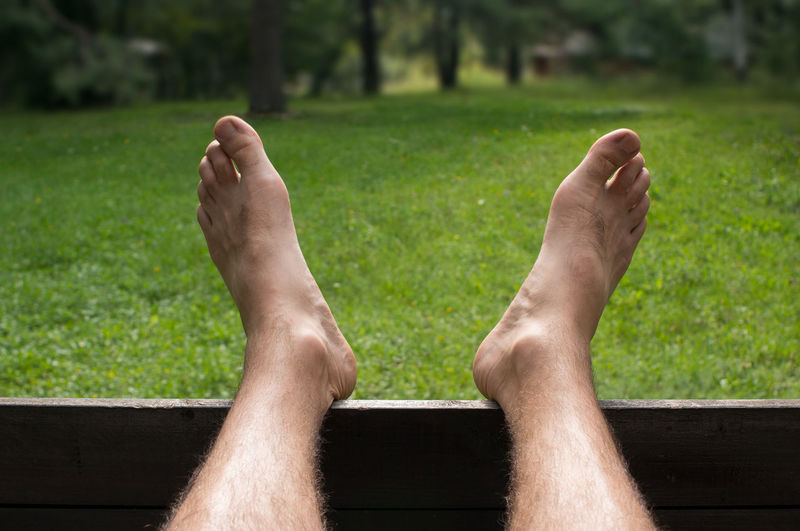Barefoot man enjoying a green grass garden barefoot Man Connecting Nature Rest Vacation Zen Male Outdoors Relax Bare Grass Foot Lifestyle Closeup Concept person People Background Summer Green Human Legs Enjoying Garden Picnic Day Holiday Feet Meadow Field Leisure Care Park Body Lawn Fun Enjoy Spring Happiness Happy Toe Leg Vintage Sun Resting Freedom Lazy Comfortable Relaxation