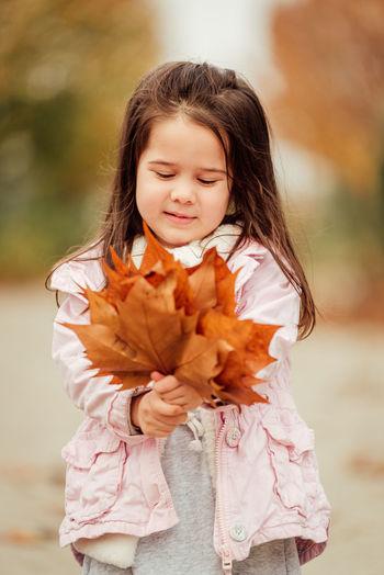 Cute girl holding autumn leaf outdoors