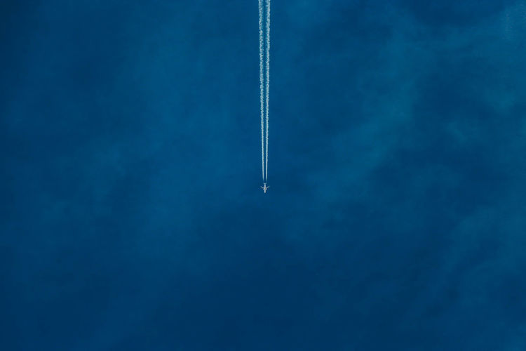 Distant view of airplane flying against blue sky