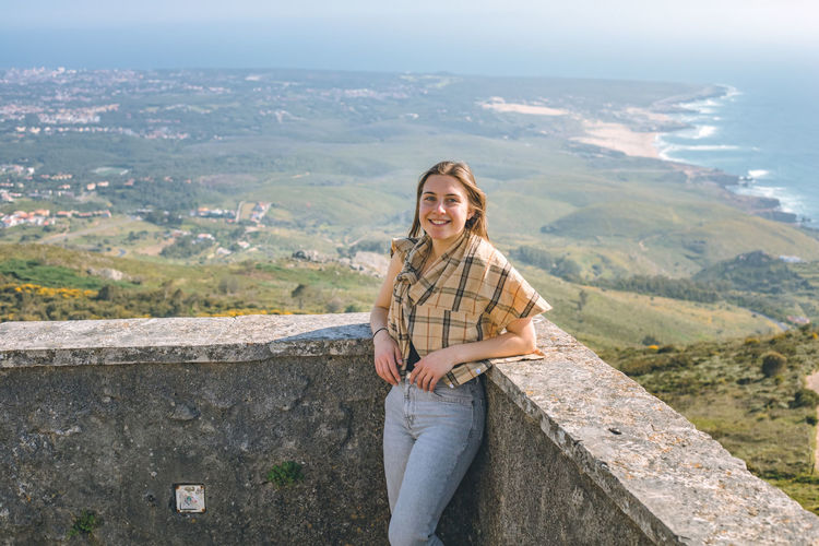 Portrait of smiling young woman against mountains