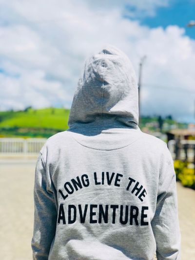 Rear view of person wearing hooded shirt with text against cloudy sky