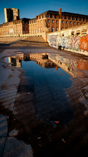 Puddle By Historic Buildings Against Clear Sky