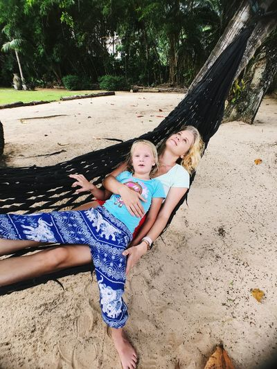 High angle view of mother and daughter on hammock at beach