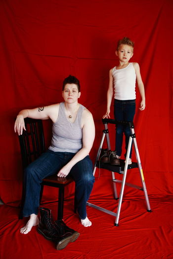 Full Length Of Mother And Son With Chairs Against Red Fabric