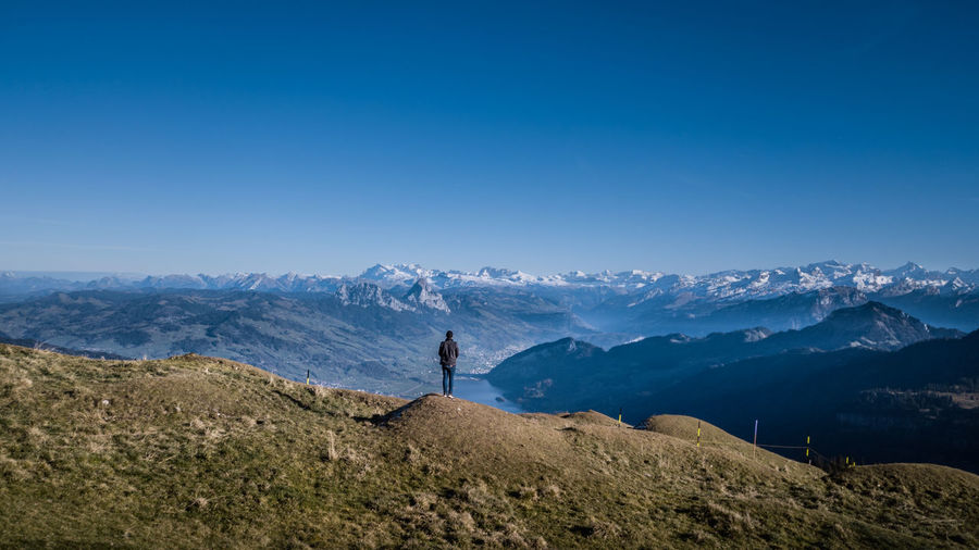 Man standing by mountains against clear blue sky