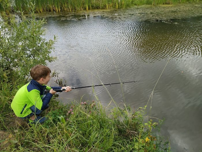 High angle view of boy fishing in lake