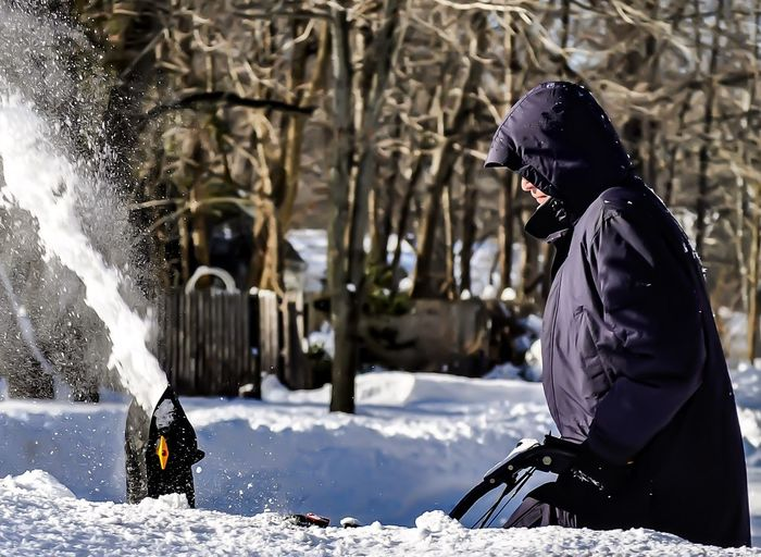 Side view of man using snowblower in winter