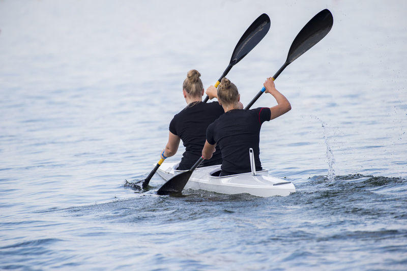 Rear View Of Female Friends Canoeing On Sea