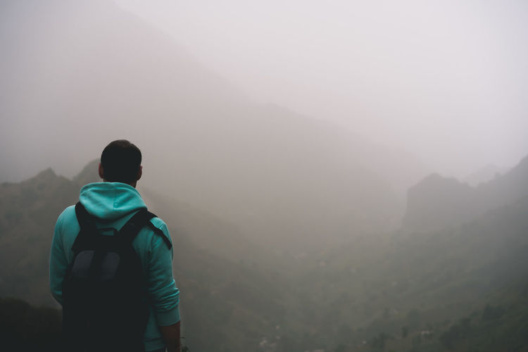 Rear View Of Mid Adult Man Looking At Mountains During Foggy Weather