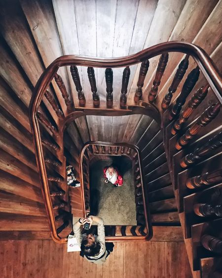 Directly above shot of man and woman standing at spiral staircase