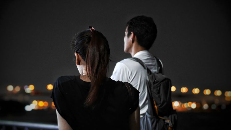 Rear view of couple standing against sky at night