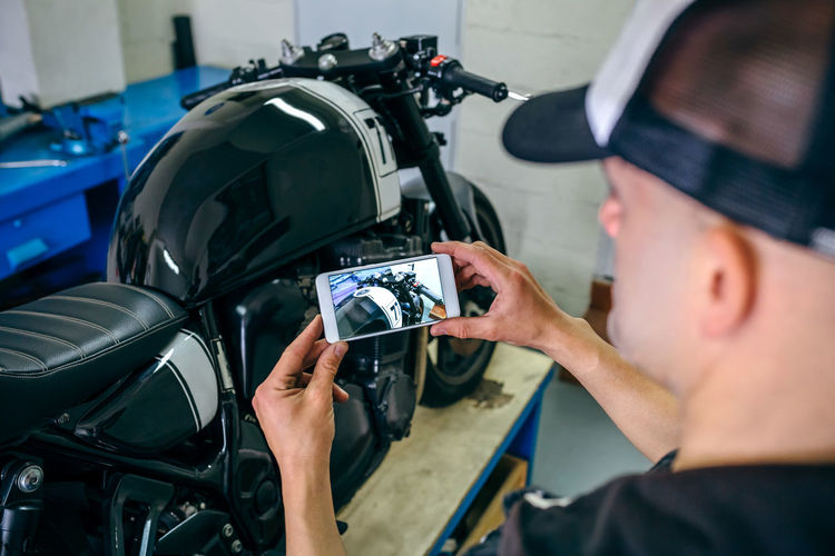 Side View Of Mature Mechanic Photographing Motorcycle In Garage