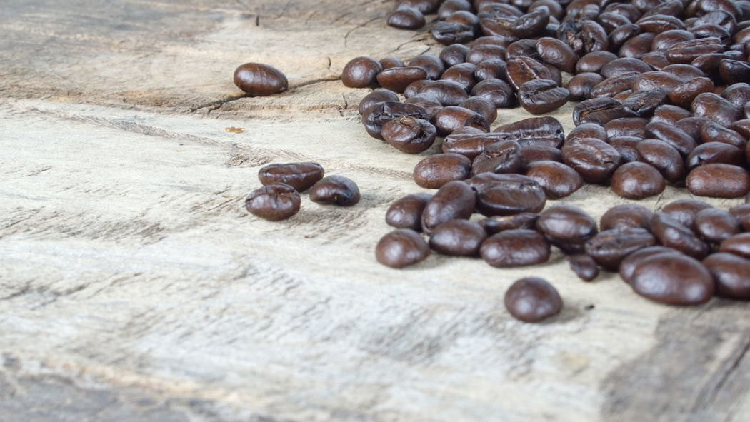Dark roasted coffee beans put on a wood table Aroma Bakery Beans Boiler Cafe Cappuccino Coffee Cookies Cream Cup Drink Espresso Fresh Headshot Latte Make Mashed Milk Morning Plate Pressure Roasted Robust Stream Table