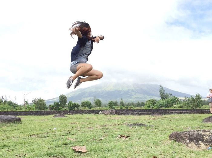 Full length of woman jumping on grass