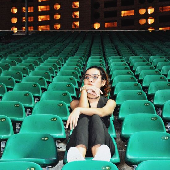 Full length of young woman sitting at stadium