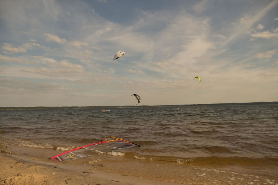Kitesurfen at the Bärwalder Lake Kitesurfen Beach Beauty In Nature Cloud - Sky Day Extreme Sports Flying Horizon Over Water Kite - Toy Leisure Activity Mid-air Nature Outdoors Parachute Paragliding Real People Sand Scenics Sea Sky Sport Tranquil Scene Tranquility Water Wave