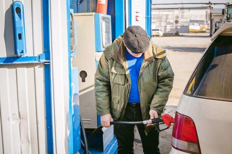 Man filling fuel in car