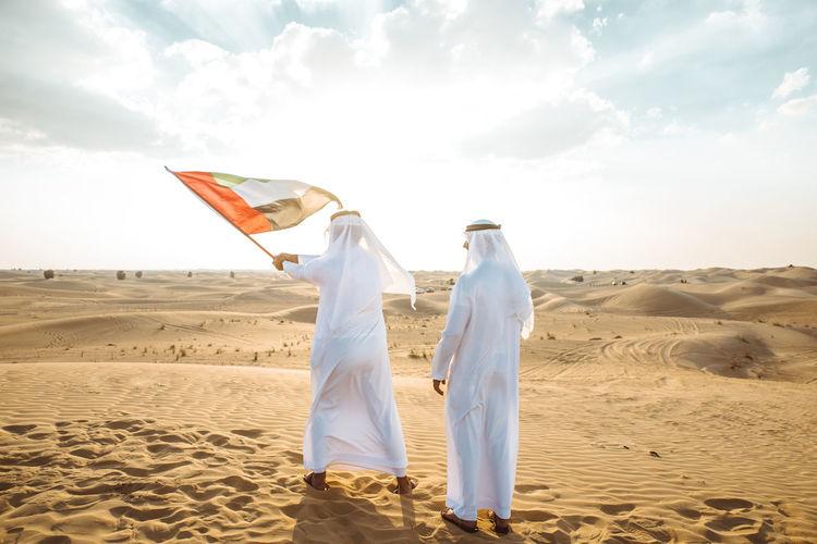 Man holding flag on sand dune against the sky