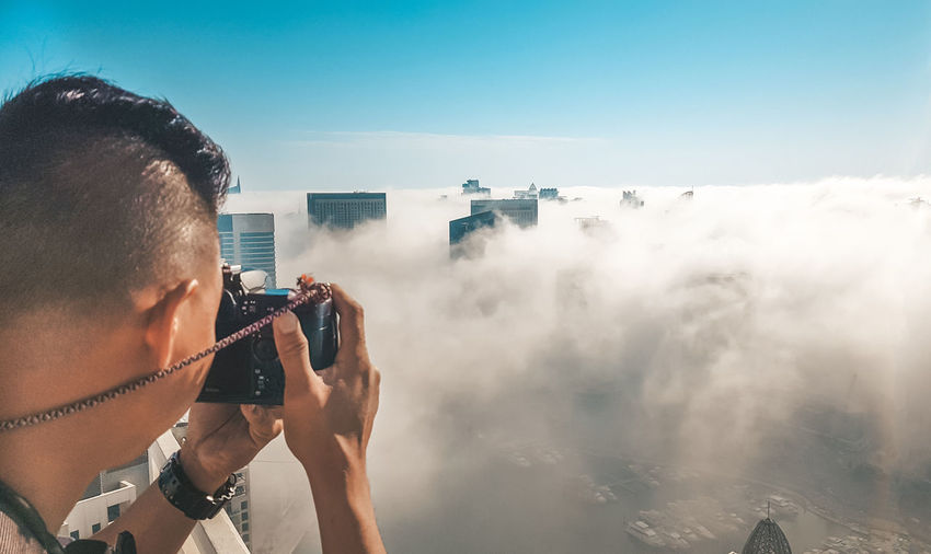 Taking photos Technology Photography Themes Photographing One Person Activity Real People Occupation Camera - Photographic Equipment Wireless Technology Lifestyles Photographic Equipment Headshot Leisure Activity Portable Information Device Digital Camera Photographer Dubai Taking Photos Dubai Fog