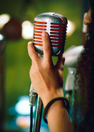 Cropped image of woman singing on microphone
