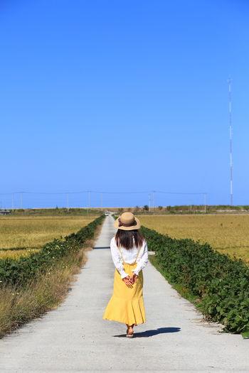 Rear view of woman walking on road amidst field against sky