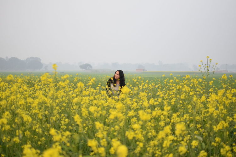 Portrait of young woman amidst yellow flowers on oilseed rape field