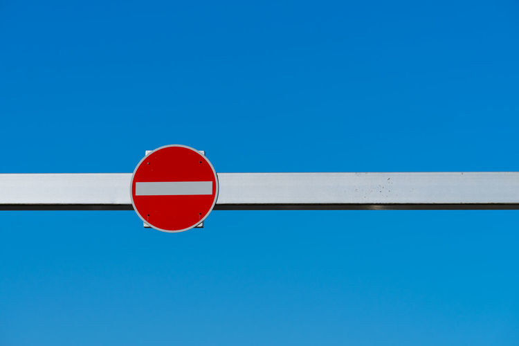 Low angle view of no entry sign against clear blue sky