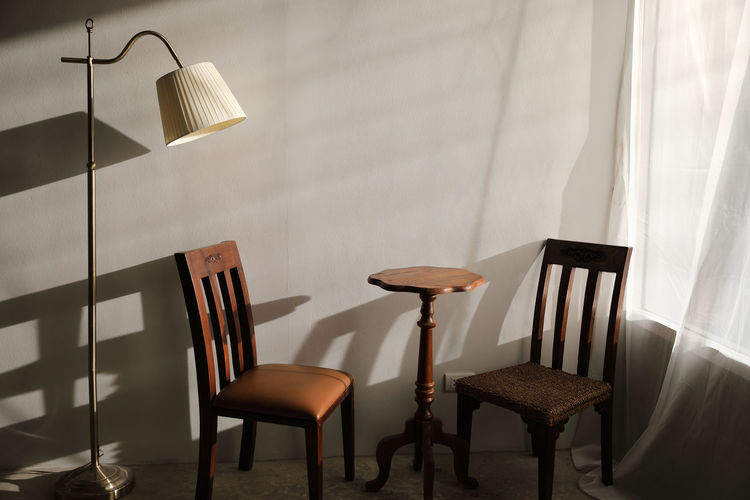Empty chairs by table against wall at home