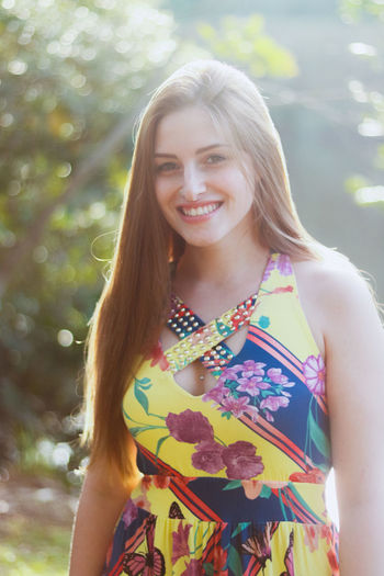 Portrait Of Smiling Young Beautiful Woman Standing At Park