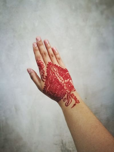 Cropped hand of woman with henna tattoo against wall