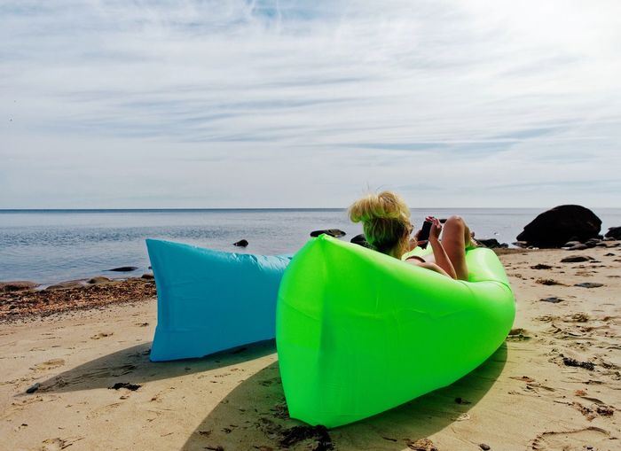 Rear View Of Woman Using Mobile Phone While Relaxing On Inflatable Chair At Beach