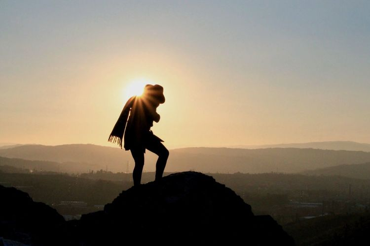 Silhouette person standing on mountain against clear sky during sunset