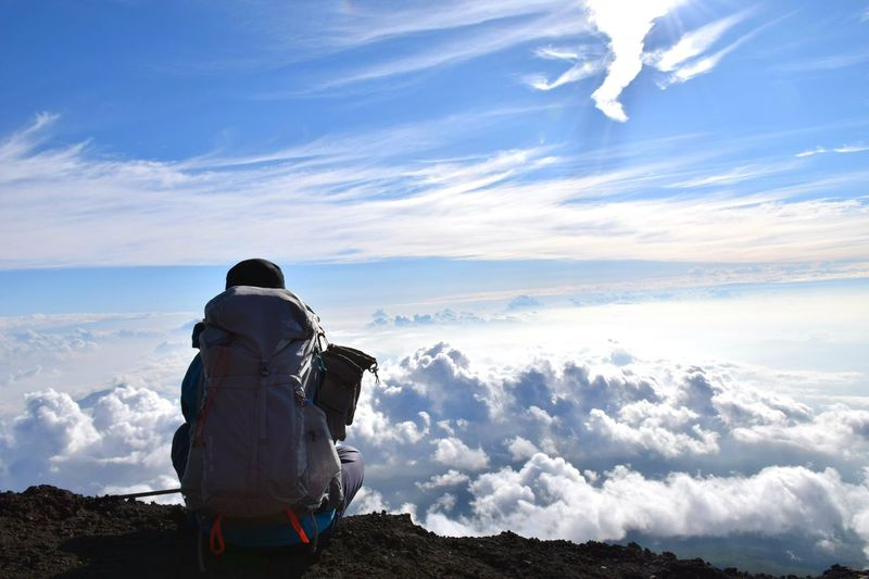 Rear View Of Man Looking At Clouds While Sitting On Mountain Against Sky