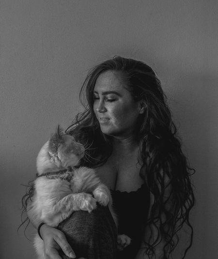 Woman holding cat while standing against wall